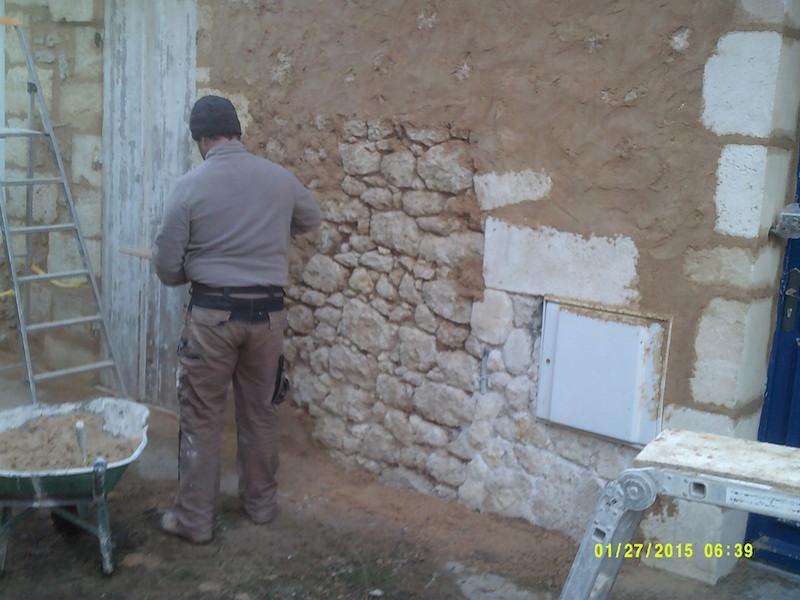 Rejointoiement en cours d'un mur en moellon